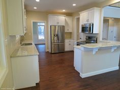 This kitchen is finished with vanilla cabinets and counters, stainless steel appliances, and hard wood floors. The Trotterville Plan 984: http://www.dongardner.com/plan_details.aspx?pid=2664. #Kitchen #HardwoodFloors #Home