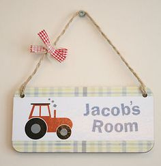 Cute Children's name plaque, with gingham patterning.   Plaque displays a quirky little tractor and a child's name, in an fun, bouncy text.  Hand finished with rope hanging and a sweet little bow.    Plaque is available with a Red tractor, Yellow tractor, Green tractor or all three tractors.