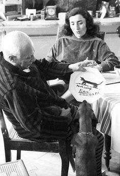 Pablo and Jacqueline Picasso, seated at a table. Picasso holds up a ceramic plate he has just painted for his dachshund, Lump. Lump, standing on his hind legs, sniffs the plate. Pablo Picasso, Picasso Art, Dog Love, Puppy Love, Francoise Gilot, Francisco Goya, Henri Rousseau, Dachshund Love, Daschund