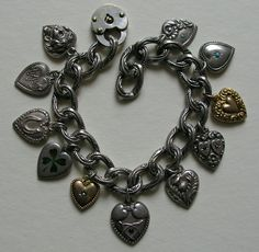 """This lovely Victorian bracelet features several hard to find antique hearts. The hearts include """"Mizpah"""", an Art Nouveau lady, horseshoe, enameled shamrock, wishbones and hearts set with a blue paste, thistle, double heart set with red pastes, two turquoise paste set hearts, two gold filled hearts and a metal lock (not sterling). Most of the hearts measure 11/16ths of an inch by 9/16ths of an inch, a few smaller and one larger. Nine of the hearts are marked sterling, two are gold filled."""
