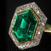Art Deco platinum and gold ring, circa 1920, with an emerald weighing 3.0 carats, surrounded by 1.0 carats of diamonds.