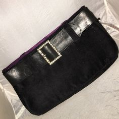 """VS Black purple bling buckle Wristlet NWT Victoria's Secret cute little evening clutch bag.  Has a leather type belt around the top with rhinestone accented bling buckle.  Body of bag is smooth fabric that almost feels like a brushed velour but a little stiffer.  Inside is purple satin with Victoria secret label.  This is from the basic instinct collection from the late 90s.  Very vintage for VS!!!!  New with tags from the gift set and never used.  Comes empty.  Measures 10"""" x 5.5"""".  Smoke…"""