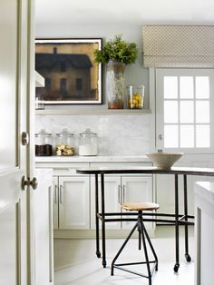 Traditional kitchen with industrial stools, bare bulb light fixtures, and framed art