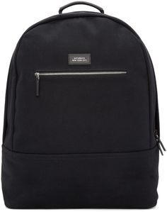Canvas backpack in black. Tonal buffed leather trim throughout. Carry handle. Adjustable padded shoulder straps. Zippered pocket and leather logo patch at face. Padded panel at back face. Zippered pockets, patch pocket, and leather logo patch at interior. Silver-tone hardware. Tonal textile lining. Approx. 17