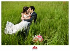 A Bride and Groom lay in the grass and kiss after their Holly Hedge Estate Wedding.