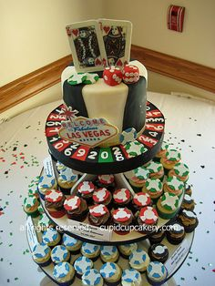 "Las Vegas Cake & Cupcakes by Cupid Cupcakery. I made this Vegas themed cake and cupcakes for a casual wedding reception after a couple got married in Las Vegas. Cake has playing cards (King and Queen of Hearts), poker chips in four colors, dice, an American roulette wheel and the famous ""Welcome to Fabulous Las Vegas"" sign.  Cupcakes were decorated with their own edible poker chips."
