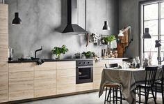 A straight-line kitchen with a row of base cabinets with ash fronts against a grey, concrete looking wall
