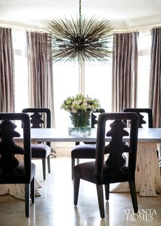 """""""Since my clients are young and hip, a formal dining room might have felt intimidating,"""" says Broaddus. She selected a zinc-top table with cypress stump bases from Groundworks and chairs custom designed by Bjork Studio. The light fixture, by Jean De Merry from R Hughes, was a splurge, she says."""