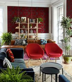 London lounge designed by HAY with modern furniture, red wallpaper, and houseplants.