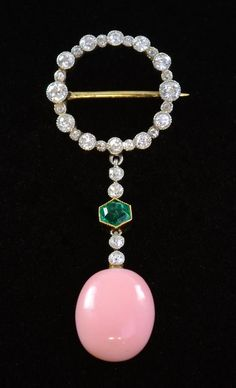 Art Deco brooch set with diamond, emerald, and conch pearl in the manner of Cartier in millgrain setting. Sold for £9400 at auction.