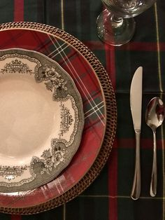 Christmas dinner table. Red tartan plates and black toile plates, both by William Sonoma. Ralph Lauren black watch plaid tablecloth. Rattan chargers. Design by Evans Construction and Design.