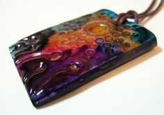"""Reaching for the sun"" necklace by Wandie Ortiz. Not a tutorial as such rather an explanation of how her finished product resembles ceramic glazes. Wandie says, ""I specialize in painting on polymer clay ... This is accomplished by applying alcohol inks (which is a dye), and alcohol medium, and painting directly onto polymer clay with a brush. Liquid clay is added to seal the color and heat as many times as needed to get the desired look I want."" Fabulous I think!"
