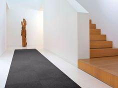 Moderne gang met kunst en fraaie trap. Deze mooie en strakke gang heeft een aantal zeer fraaie details. Naast het kunstwerk valt allereerst natuurlijk de trap op, waarvan de treden van het zelfde hout zijn gemaakt als het beeld. De trap lijkt dankzij de dichte balustrade te verdwijnen in de hoogte. Door het ontbreken van een leuning is het trouwens verstandig om de muren naast de trap te schilderen met gewone verf, die is namelijk makkelijker schoon te houden. In de gang ligt een mooi ...