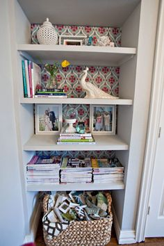 Line the back of bookshelves using fabric covered cardboard...no damage & you can swap out when you change colors...I think we have a winner!!