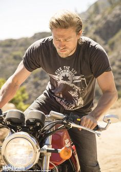 Saddling up: Charlie Hunnam shows off his biking skills in the pages of Men's Health magaz...