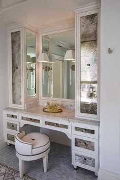 Glam dressing room features a built-in dressing table with antiqued mirrored drawers topped with marble countertops paired with a round vanity stool situated under vanity mirror illuminated by The Urban Electric Co Melissa Quartz Light flanked by antiqued mirrored cabinets.