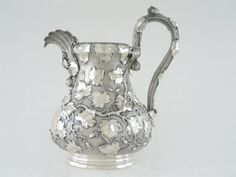 "An American coin water pitcher with a maker's mark of Vincent Laforme & Brother, retailer's mark of Jones, Ball & Poor, Boston, Circa 1850. Pear-shaped, with blossom and branch handle, chased with ivy vines against a stippled ground, enclosing cartouche opposite the handle, engraved with a monogram JR; Height is 11 1/2"" inches, Weight is 33.80 Troy ounces"