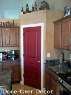 Done Over Decor: Painted Pantry Doors. We painted our cranberry to match the other red accents in our kitchen. Wow! What a difference.