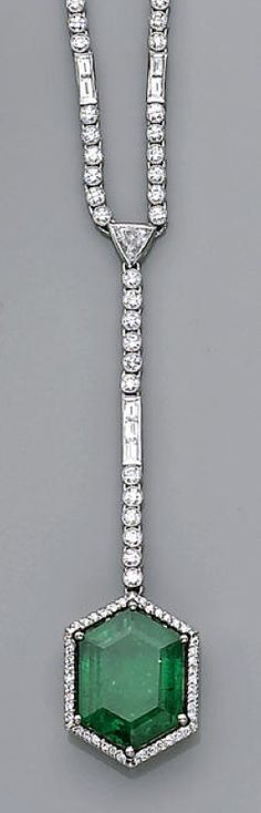 An emerald and diamond necklace  designed as a diamond chain of alternating baguette-cut two-stone and round brilliant-cut five-stone links, suspending a pendant of similar design with a hexagonal-cut emerald and diamond terminal; emerald weighing approximately: 7.30 carats; estimated total diamond weight: 5.75 carats; mounted in platinum; length: 17¾in.