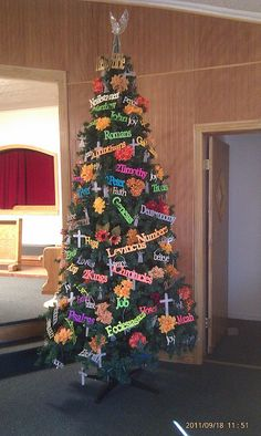 Church seasonal tree decorated with Bible book names in fall colors. Names were cut with Cricut machine. Flowers and other decor items added.