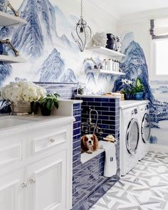 Washing the pup and doing the laundry would be downright enjoyable in a laundry room as lovely as this! Delft subway tiles mimic the blue traditionally used for Chinese ginger jars. And actually, ginger jars, or antique apothecary jars (!!) would be beautiful ways to storage laundry supplies, and would echo not only the marvelous Chinese mountains wallpaper, but also the vintage Seguso Murano caged glass pendant light, which is pretty glam above the low utility sink/dog shower. The wallpaper…