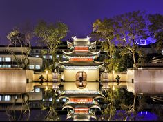 China Nanjing ancient confucius temple front view illuminated with lights at sunset with reflection in still pool with water