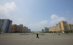 """A view of Pyongyang streets, with a glimpse of the Ryugyong Hotel, a 1,083-foot tall skyscraper that was abandoned in mid-construction in 1992. (center, pyramid-shaped building in the distance.) Eric Lafforgue: """"On Sundays, cars are not allowed in Pyongyang. Only vehicles belonging to the army and government are allowed on the road. Officials claim that it's to prevent pollution."""""""