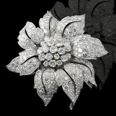 Flowerhead diamond clip brooch consiting of central brilliant cut diamond clusterto a pave set diamond eight leaf surround each with pierced spine by Bvlgari, Rome c.1960's