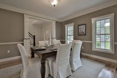 433 Davis Road, Bedford, MA —This dining room captures the perfect balance between formal and casual with slip covered chairs and fresh gray paint contrasted with gleaming white chair rails and dentil crown moulding.
