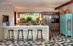 Tanto a bancada quanto as paredes da cozinha gourmet têm acabamento de cimento queimado. Durante a execução da laje, embutiram-se pontos de luz no teto. Abajures feitos pelos moradores complementam a iluminação. Projeto do escritório Vida de Vila.