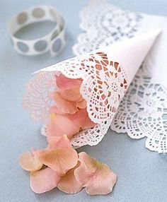 Roll Doilies and fill with rose petals for throwing down the aisle