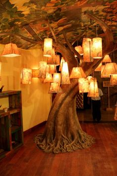 A tree magically grows inside a room, festooned with lanterns