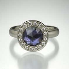 Get colorful with Anne Sportun's 14K white gold bezel set blue sapphire solitaire surrounded by diamonds! It is a perfect selection for the modern, classic bride!