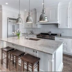 Love the wood barstools against the white cabinets