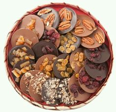 Box with mendiants or chocolate disks covered with fruits Caja con mendiants o discos de chocolate cubiertos de frutos secos. Box with mendiants or chocolate disks covered with nuts.