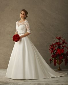 6530 from our Love Collection by Bonny Bridal - Traditional perfection with a modern twist. Beautiful scrolled lace frames the bodice with sheer details. Elbow length sleeves. Full light satin skirt with pockets.