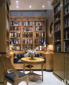 A small library, where Elton John displays photographs of friends and family, features a Biedermeier-style birch-and-ebony banquette, an 1820s Russian Empire chair, and a 1920s Swedish birch table | archdigest.com