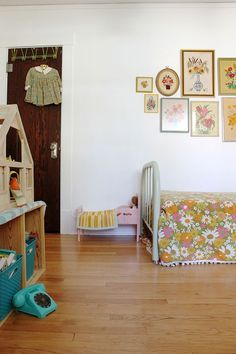 I love this vintage-y kids room, especially the floral bedspread & embroidery wall