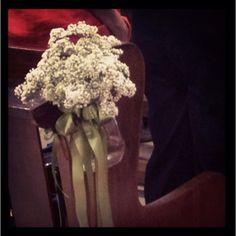 Flowers along the isle in a church wedding
