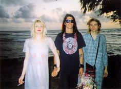 Kurt Cobain and Courtney Love were married on Waikiki Beach in Hawaii at the end of Nirvana's Pacific Rim tour in Love's satin dress was previously owned by troubled actress Frances Farmer. Dave Grohl stands inbetween bride and groom. Dave Grohl, Courtney Love Kurt Cobain, Nirvana Kurt Cobain, Kurt Cobian, Celebrity Wedding Dresses, Celebrity Weddings, Frances Farmer, Historia Do Rock, What A Nice Day