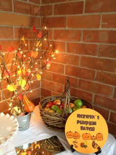 Fall party decor, branches, leaves, and lights in a bucket, apples in a basket or bucket