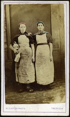 Occupation: Workers at the Tredegar Ironworks. Women were forbidden to go down the mines but could be employed in heavy industry on the pit face. Tinted photo. Note jewelry, sleeve detail, but heavily used aprons.  by W Clayton of Tredegar, Wales, 1865.