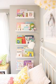 I use these same shelves in my bedroom to hold all my perfume bottles.  Shelves available at Ikea in the picture frame sections.  Book selves facing outward to see the book cover.