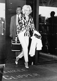21 Feb 1962, Ft. Lauderdale, Florida, USA --- Marilyn Monroe, shown rushing out of Yankee Clipper Hotel here February 20 after visiting the Yankee Clipper, Joe DiMaggio. DiMaggio is here as an instructor for New York Club. --- Image by © Bettmann/CORBIS