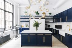 Modern Kitchen Interior Moody blue cabinets with brass pulls and a dramatic bubble chandelier create an elevated communal kitchen. - Moody blue cabinets with brass pulls and a dramatic bubble chandelier create an elevated communal kitchen. Interior Design Kitchen, Modern Interior Design, Interior Design Inspiration, Design Ideas, Design Trends, Contemporary Interior, Kitchen Contemporary, Transitional Kitchen, Blog Design