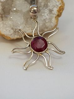 """Sunburst pendant with round faceted Indian Ruby center stone, bezel-set in delicate 925-hallmarked sterling silver. Length: 2"""" including bail. Width: 1.5"""""""