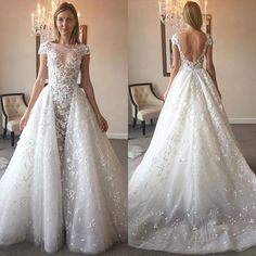 Here is a beautiful short cap sleeve wedding gown that has pretty embellishments. The detachable over skirt adds to the design. Get custom #weddingdresses and #replicas of haute couture dresses for less with our firm. Email us for pricing. Dariuscordell.com