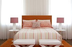 pink white bedside lamps on the top of tulip side tables flank an orange bed, form the feminine bedroom decor
