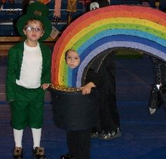 Brief Description:  Our daughter wanted to be a rainbow for halloween so we came up with the idea of a leprechaun with his pot of gold and rainbow. I got help with the sewing of the pattern from grandma and made the pot to fit my daughter  Materials:  black and gold spray paint  pot  colored streamers  plastic gold coins  hot glue  straps or ropes  black leggings and shoes  long white socks & white t-shirt  black shoes  pattern for top hat, jacket, and shorts (same as Uncle Sam)  green…