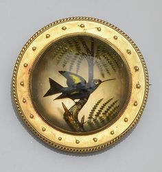 The circular rock crystal cabochon reverse carved and painted to depict a blue and yellow hummingbird, seated on a fern branch, in a bloomed gold mount with applied bead and ropetwist detail, glazed locket verso,